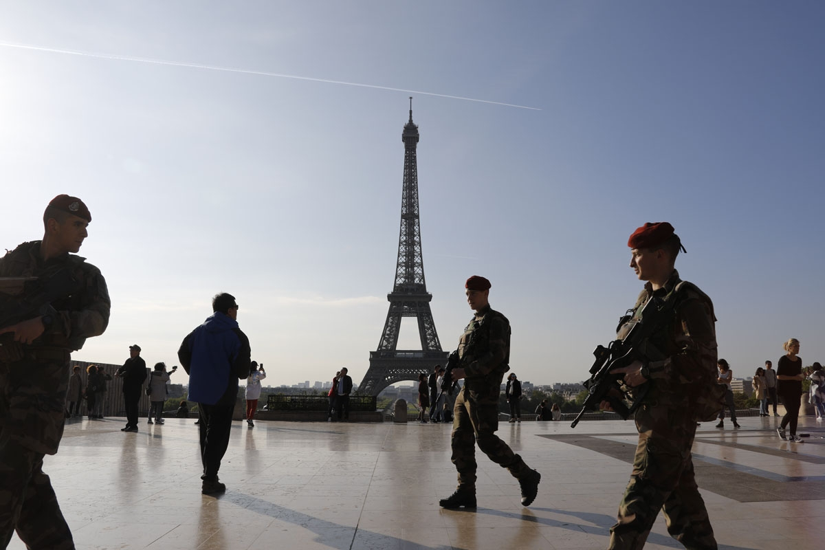 French soldiers of the Operation Sentinelle patrol on the Human Right square in front of the Eiffel tower in Paris, on April 23, 2017, as France vote for the first round of the presidential election.