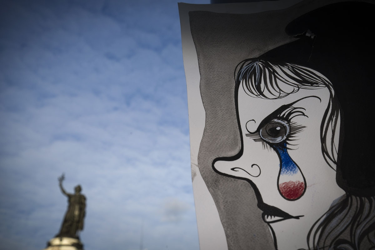 A picture taken on November 22, 2015 shows a painting by French painter and graphic designer Liox picturing Marianne, the allegoric symbol of French Republic, in front of the Republic statue in Paris in tribute to the victims of November 13 attacks in Par