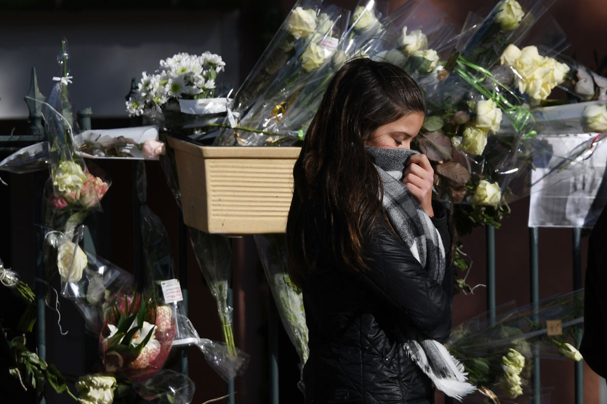 A young woman walks past white roses in front of the City Hall of Saint-Feliu-D'Avall during a ceremony on December 17, 2017 in memory of the five children killed in a collision between a train and a school bus on December 14.
