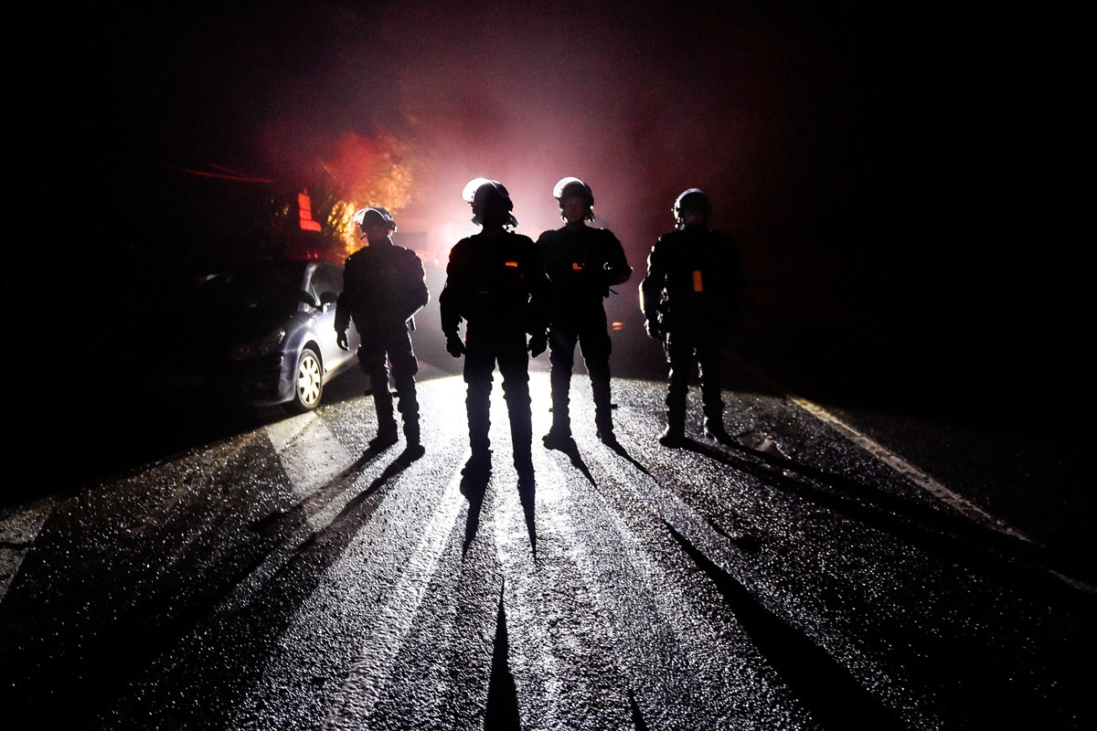 French riot police officers stand guard during the eviction of environmental protesters from the site, known as ZAD (Zone a Defendre - Zone to defend) of what had been a proposed new airport in Notre dame des Landes on April 9, 2018.