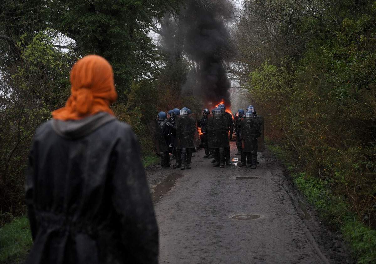 A protester looks towards a group of riot police during the eviction of environmental protesters from the site, known as ZAD (Zone a Defendre - Zone to defend) of what had been a proposed new airport in Notre dame des Landes on April 9, 2018.