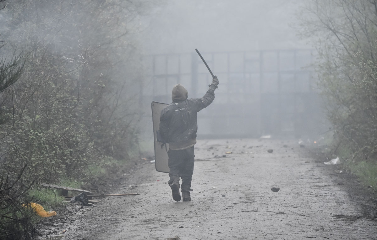 A protestor holds a police riot shield and a baton as French police officers move in to clear the area during the eviction of environmental protesters from the site, known as ZAD (Zone a Defendre - Zone to defend) of what had been a proposed new airport i
