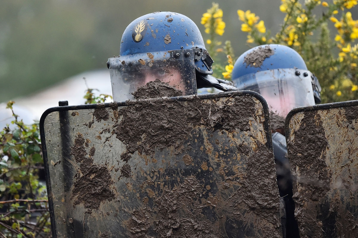 French gendarmes gather behind riot shields as they clash with ZAD activists to clear an area known as ZAD (Zone a Defendre - Zone to defend) of environmental protesters occupying the site of what had been a proposed new airport in Notre dame des Landes