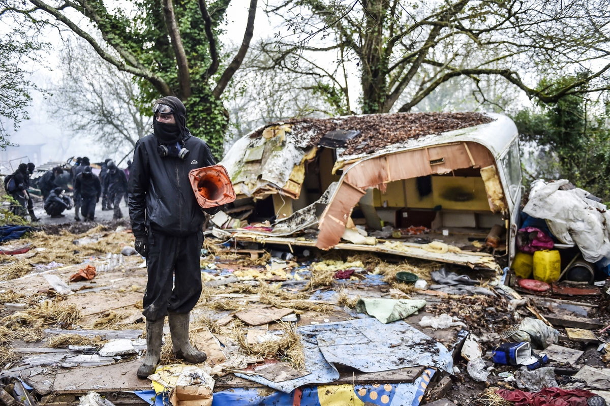 A protester stands in the rubble destroyed houses on April 10, 2018 during a police operation to raze the decade-old camp known as ZAD (Zone a Defendre - Zone to defend) at Notre-Dame-des-Landes, near the western city of Nantes, and evict the last of the