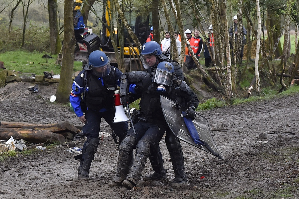 An injured riot gendarme is helped by comrades when clashes erupt with protesters on April 10, 2018 during a police operation to raze the decade-old camp known as ZAD (Zone a Defendre - Zone to defend) at Notre-Dame-des-Landes, near the western city of Na