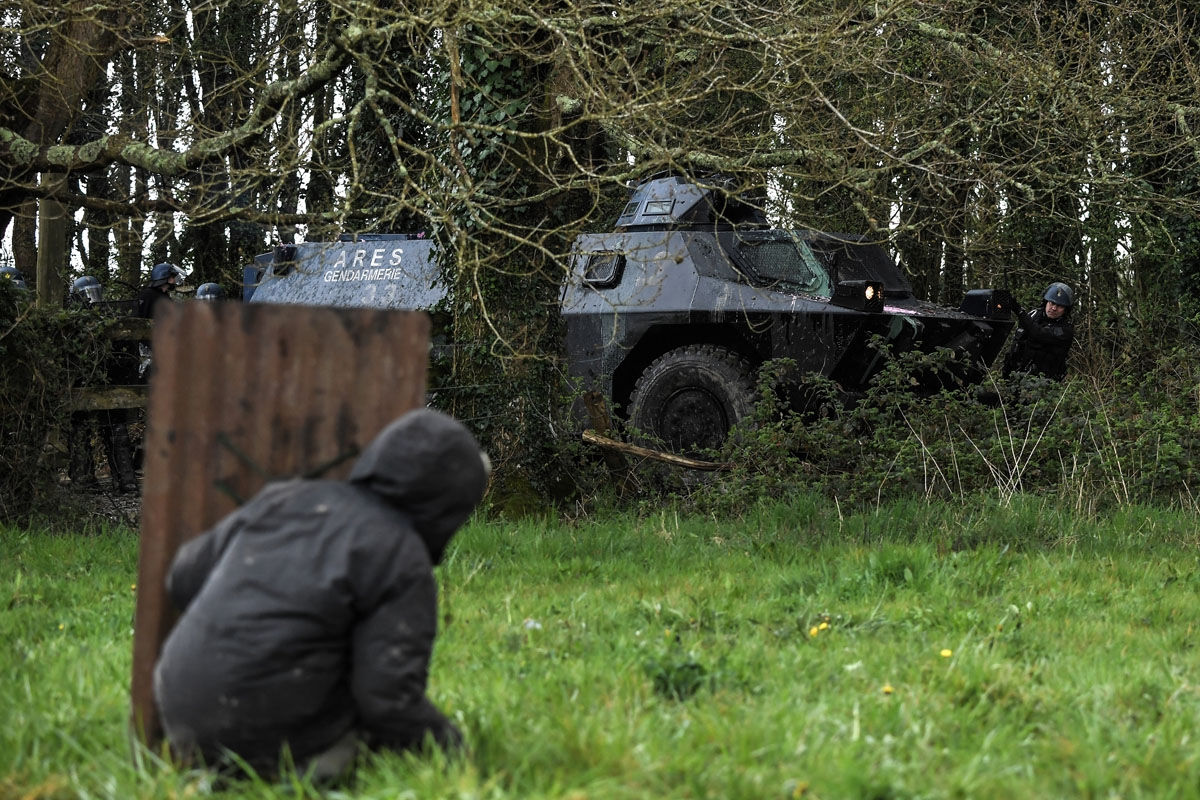 A protester behind a makeshift shield faces riot Gendarmes and their armoured vehicul on April 10, 2018 during a police operation to raze the decade-old camp known as ZAD (Zone a
