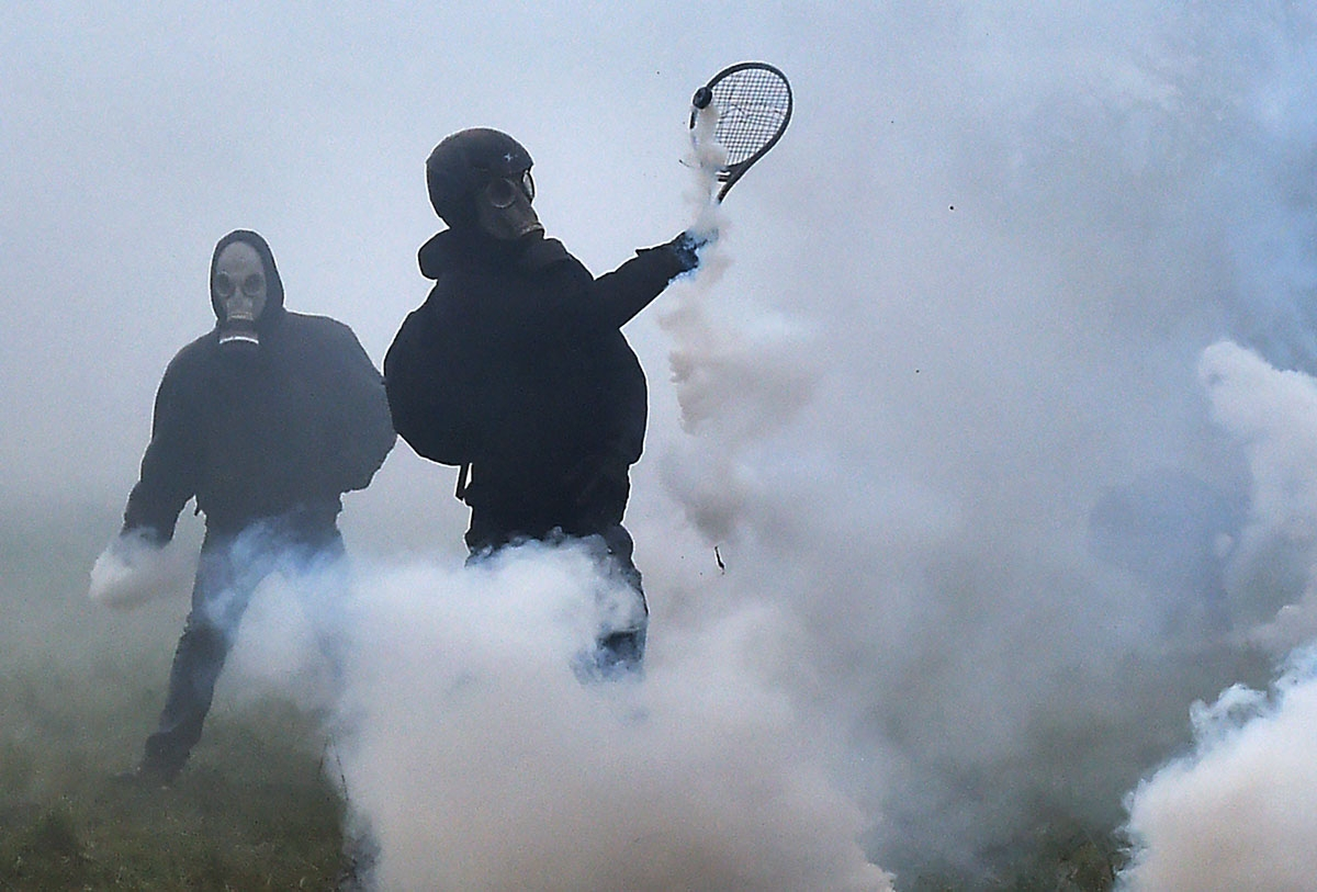 A protester uses a tennis racquet to defend himself from teargas canisters released by riot forces as clashes erupt during a police operation to raze the decade-old camp known as ZAD (Zone a Defendre - Zone to defend) at Notre-Dame-des-Landes, near the we