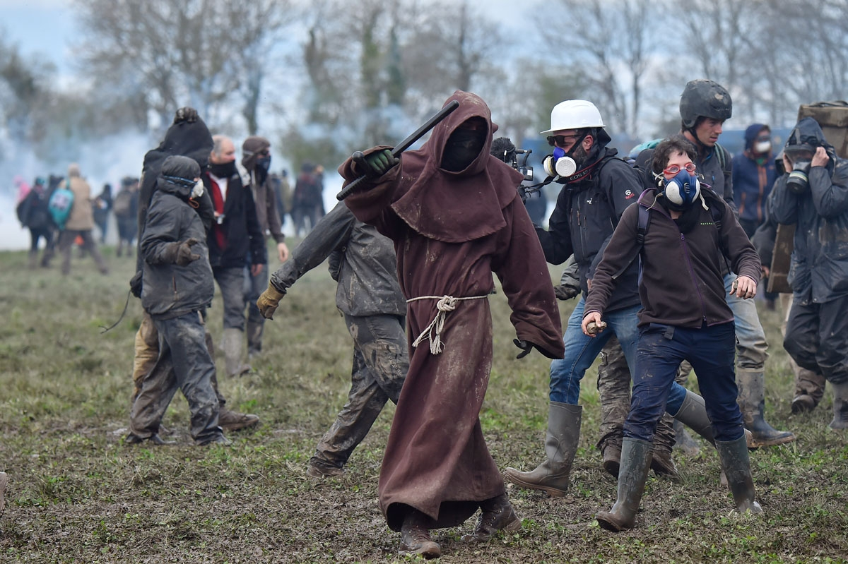 A protester dressed as a monk walks holding a police baton on April 11, 2018, during a police operation to raze the decade-old anti-capitalist camp known as ZAD (