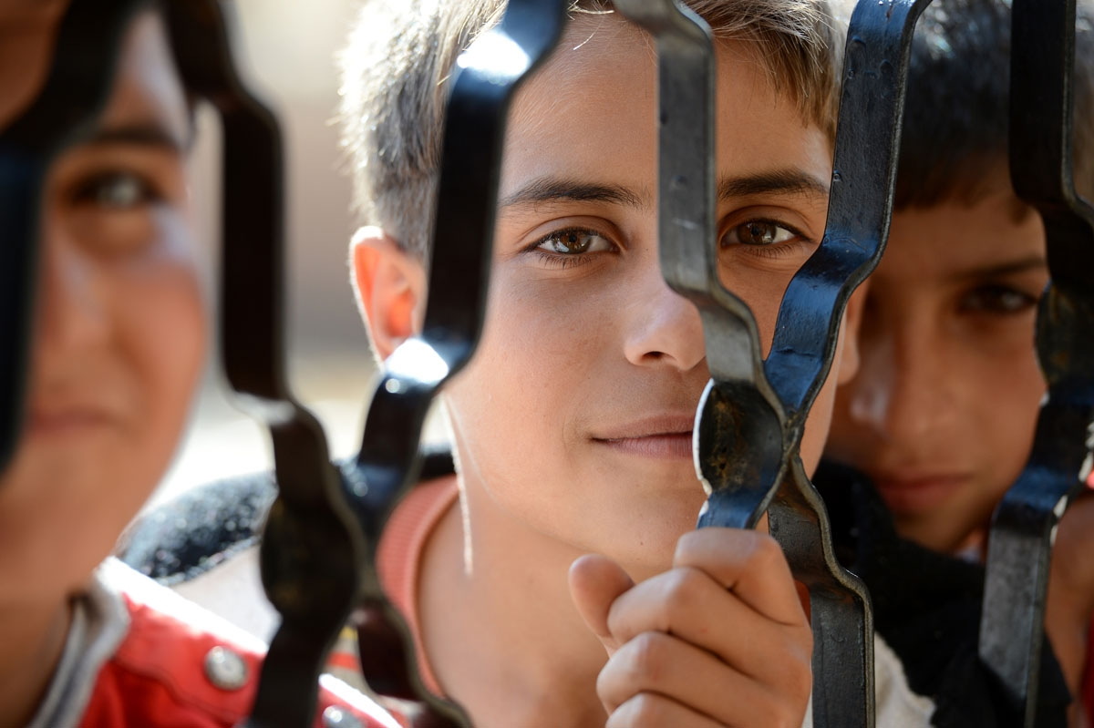 Syrian boys wait for food behind an iron door at a school housing around 140 refugees in the village of Atme in the Idlib province near the border with Turkey on November 6, 2012.