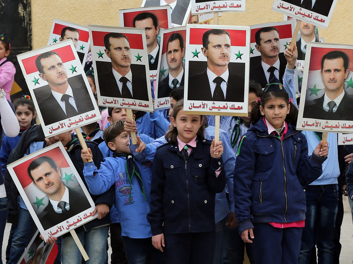 Syrian children hold portraits of President Bashar al-Assad during a gathering in support the ruling Baath party at a school in the government-held side of the northern city of Aleppo on November 17, 2014.
