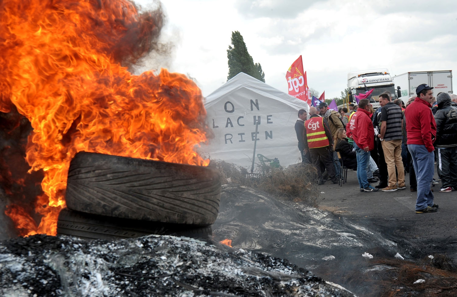 French union members burn tires as they protest against the proposed government labour reforms outside a petrol depot at Douchy-Les-Mines, northern France, on May 24, 2016