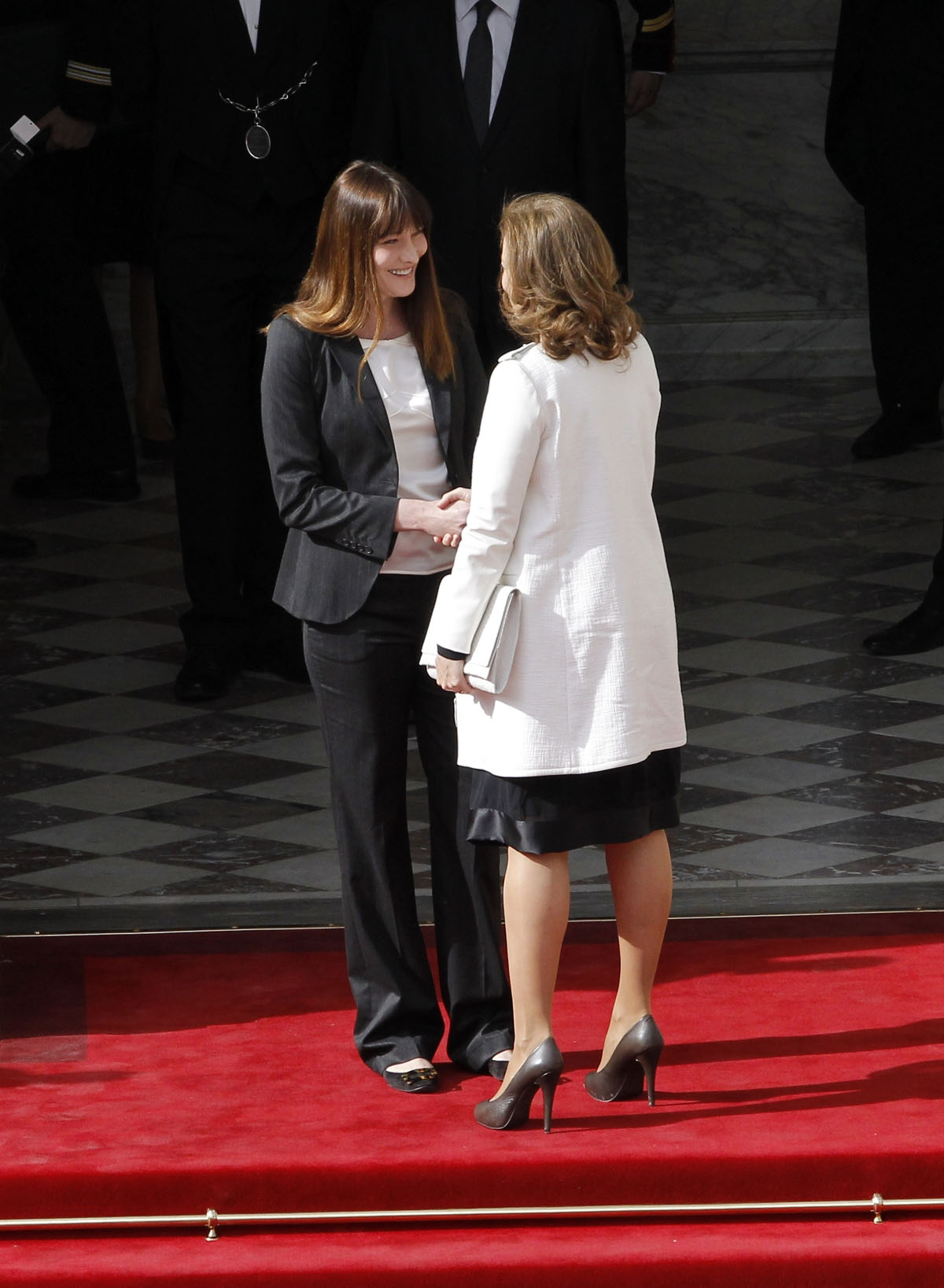 French outgoing First Lady Carla Bruni (L) welcomes Valerie Trierweiler, companion of France's President-elect Francois Hollande, prior to the start of the investiture ceremony between France's president Francois Hollande and his predecessor Nicolas Sarko