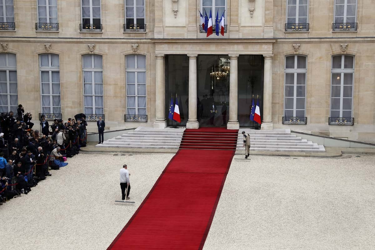 Employees rake the courtyard near the red carpet as journalists (L) wait at the entrance of the Elysee presidential Palace prior to the Emmanuel Macron's formal inauguration ceremony as French President on May 14, 2017 in Pari