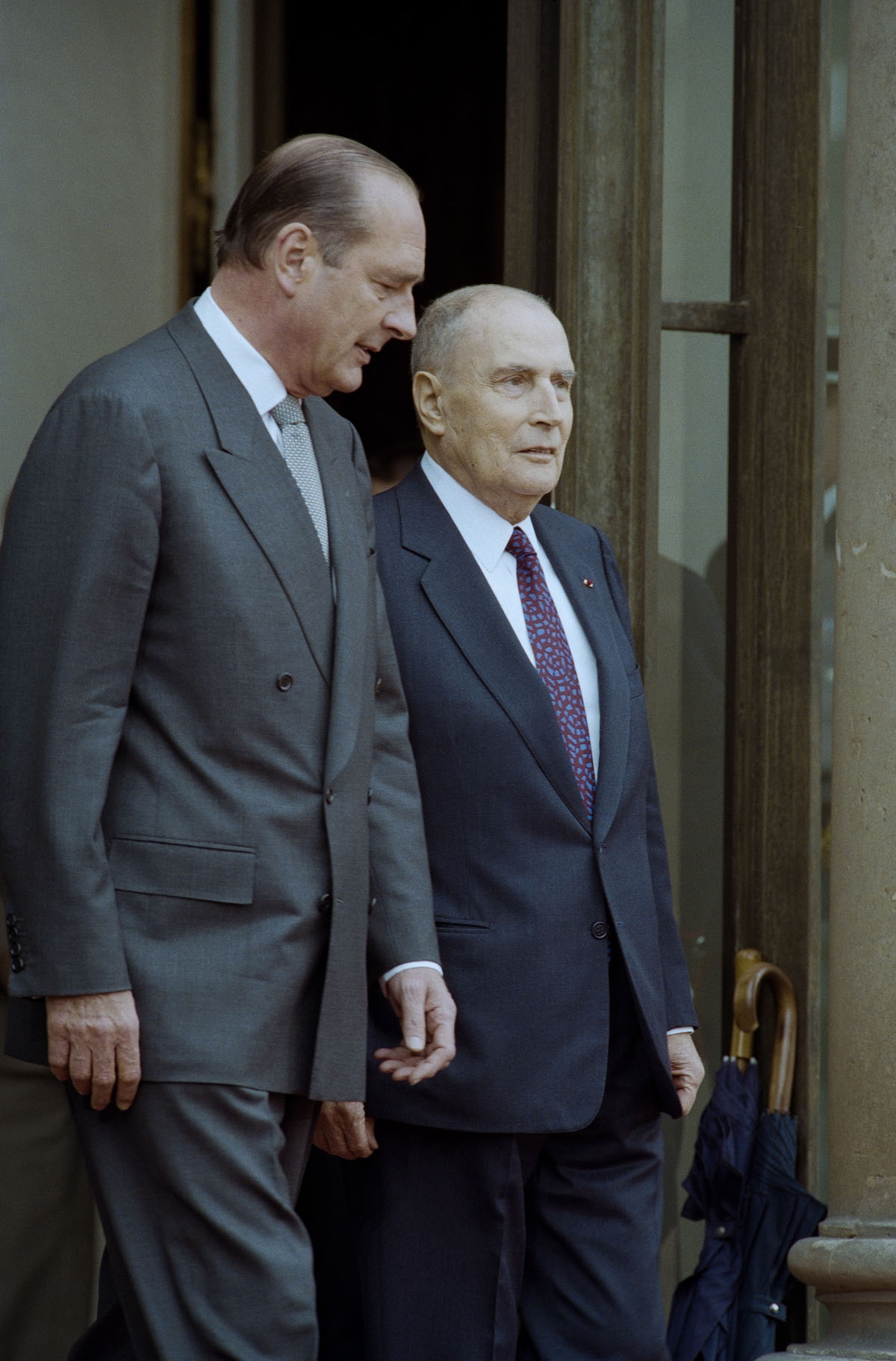 . France's President-elect Jacques Chirac (L) goes with his predecessor François Mitterrand on the doorstep at the Elysee Palace during the formal handover of power ceremony on May 17, 1995 in Paris.