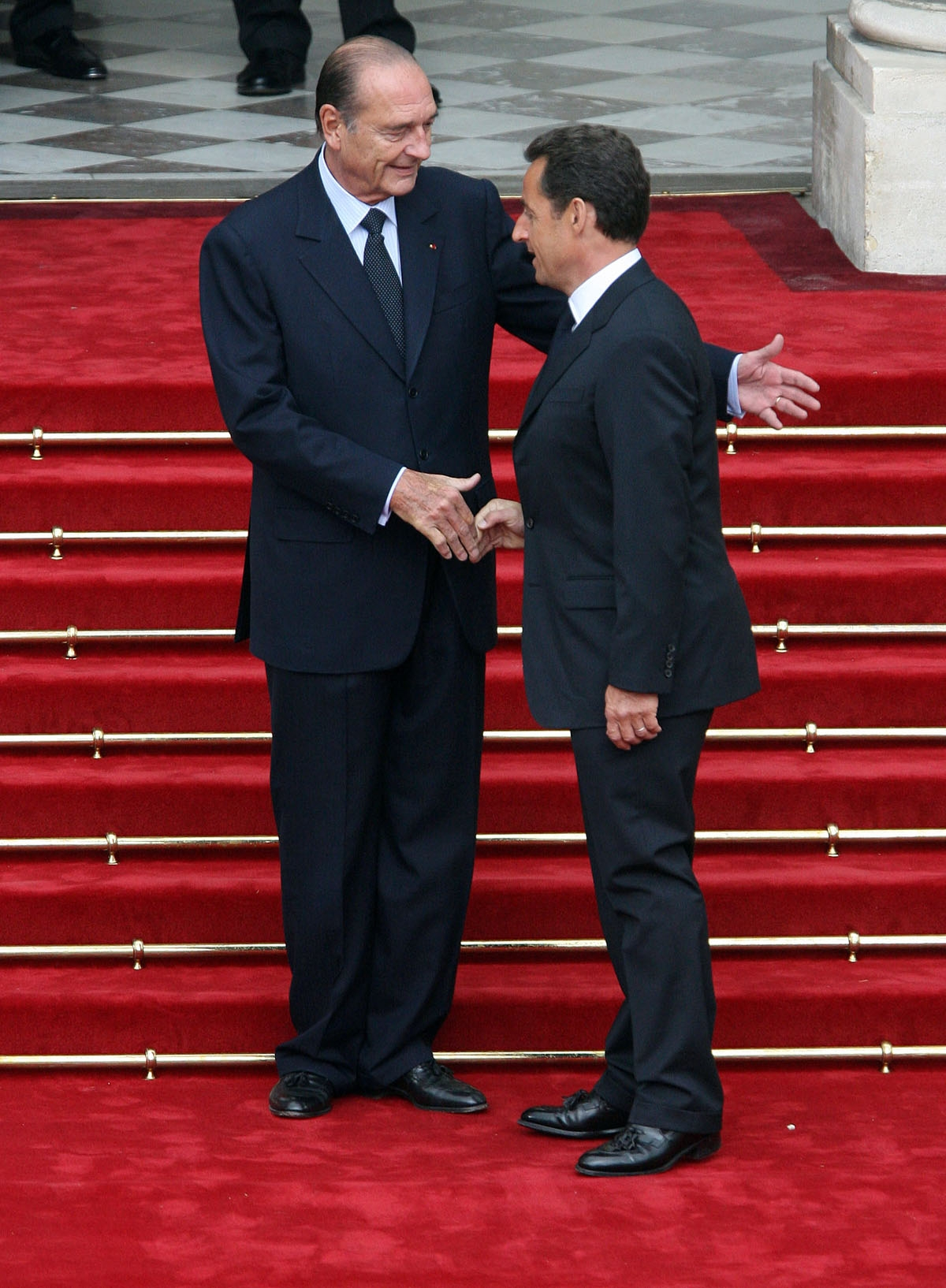 French president Jacques Chirac (L) welcomes his  successor Nicolas Sarkozy upon his arrival at the Elysee Palace for the formal handover of power ceremony, 16 May 2007 in Paris.