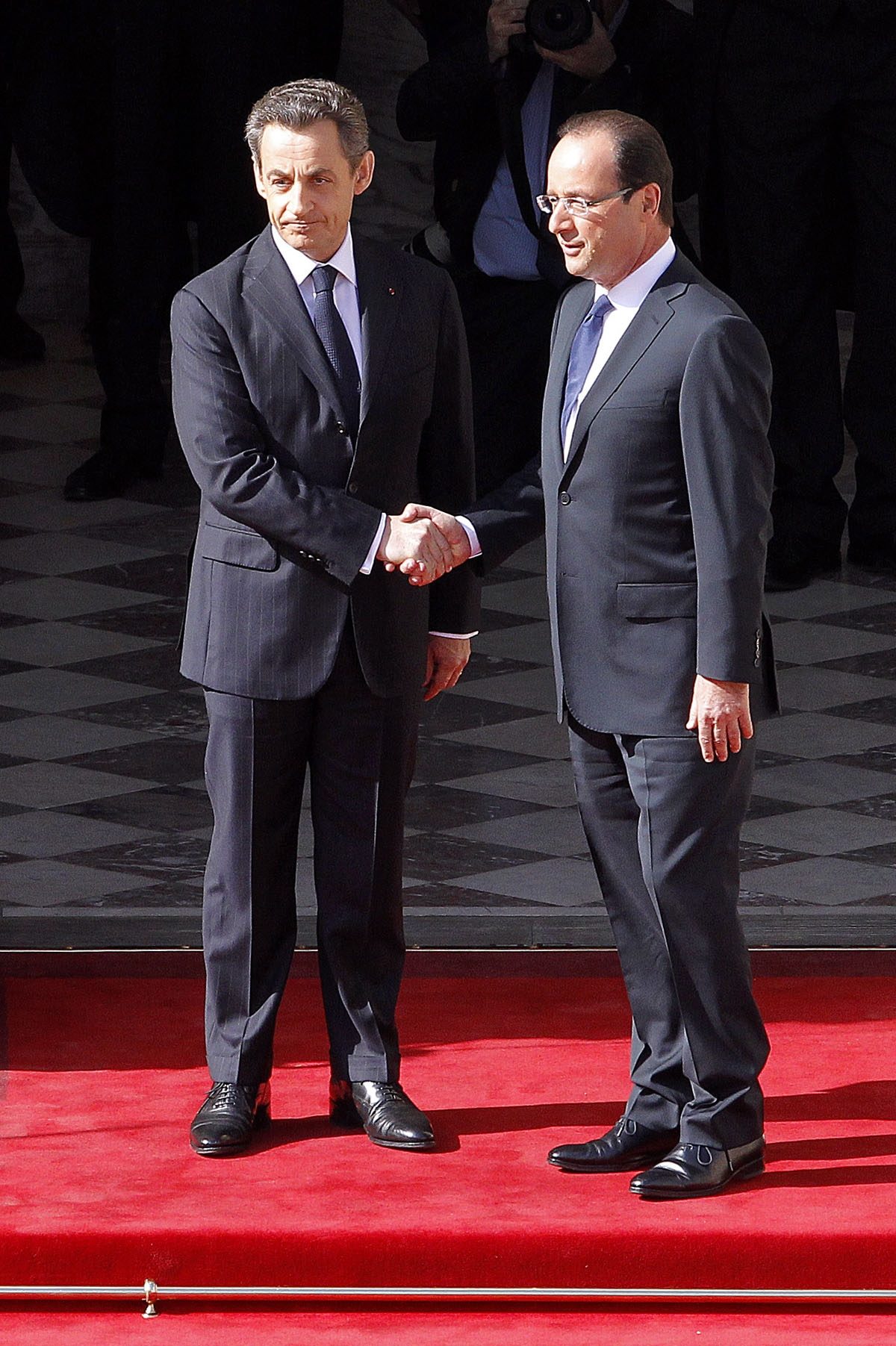France's President Francois Hollande (R) shakes hands with his predecessor Nicolas Sarkozy (L) prior to the start of the investiture ceremony on May 15, 2012 at the presidential Elysee Palace in Paris.