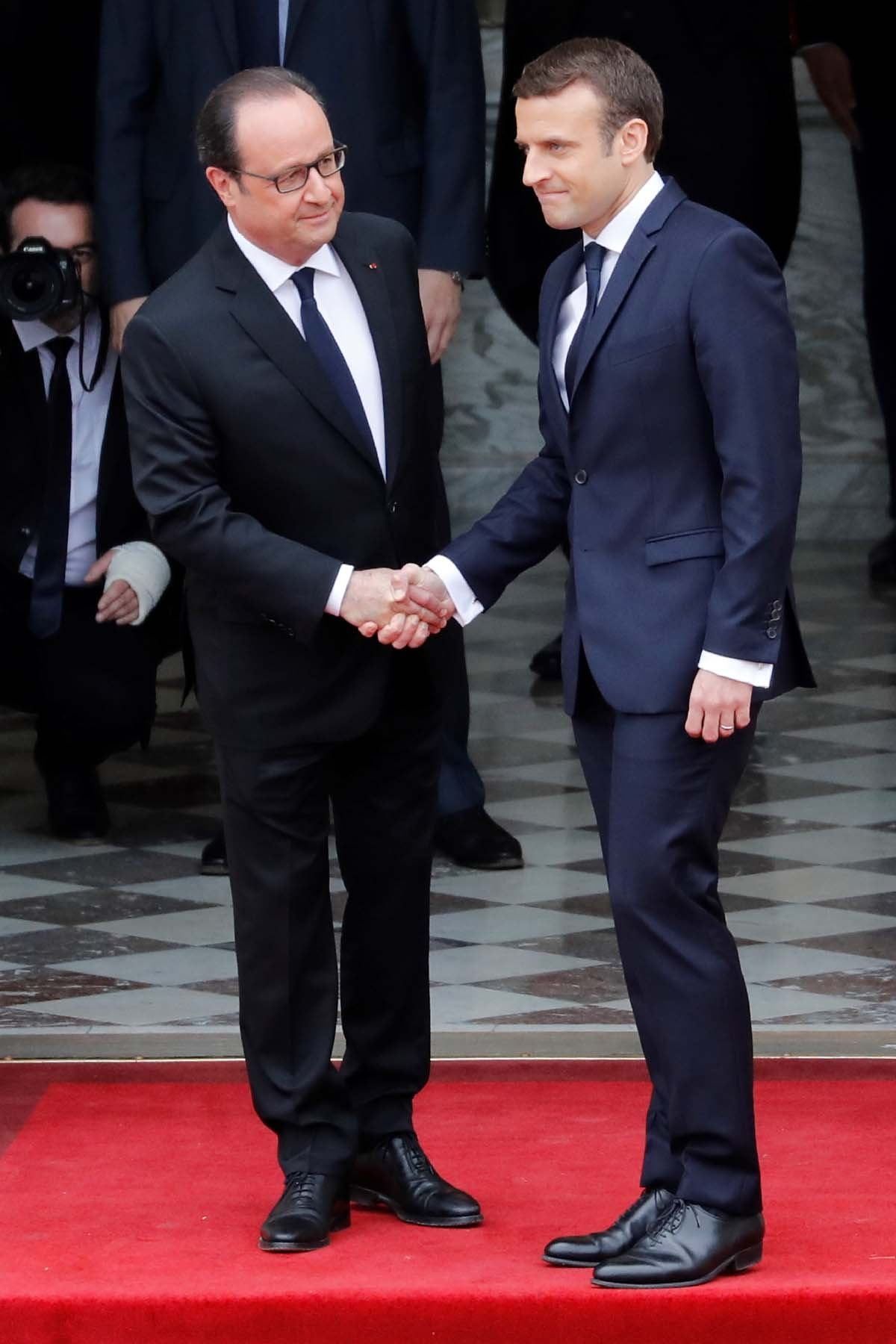 French newly elected President Emmanuel Macron (R) is welcomed by his predecessor Francois Hollande as he arrives at the Elysee presidential Palace for the handover and inauguration ceremonies on May 14, 2017 in Paris.