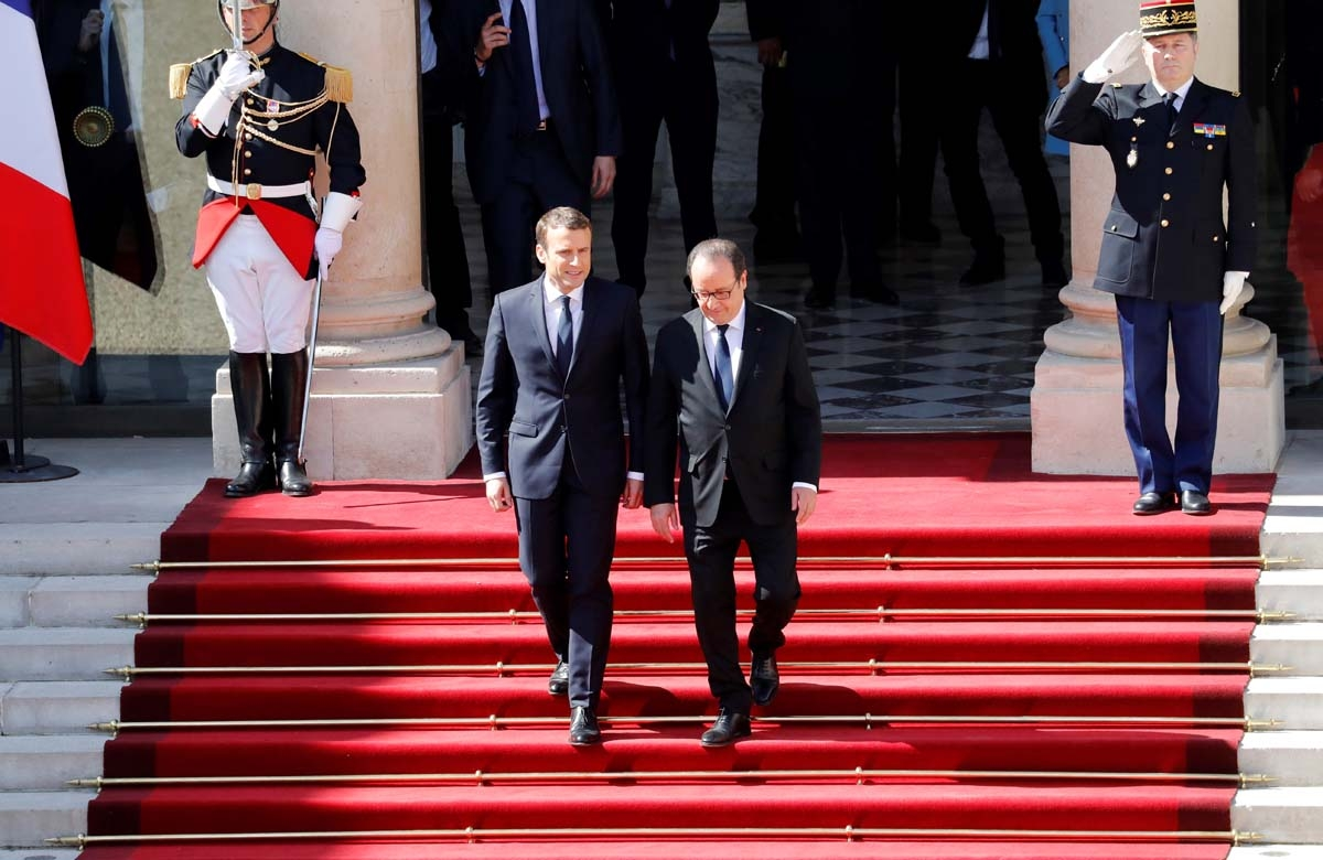 French outgoing President Francois Hollande (R) is escorted by his successor Emmanuel Macron as he leaves the Elysee presidential Palace at the end of their handover ceremony and prior to Macron's formal inauguration as French President on May 14, 2017 in