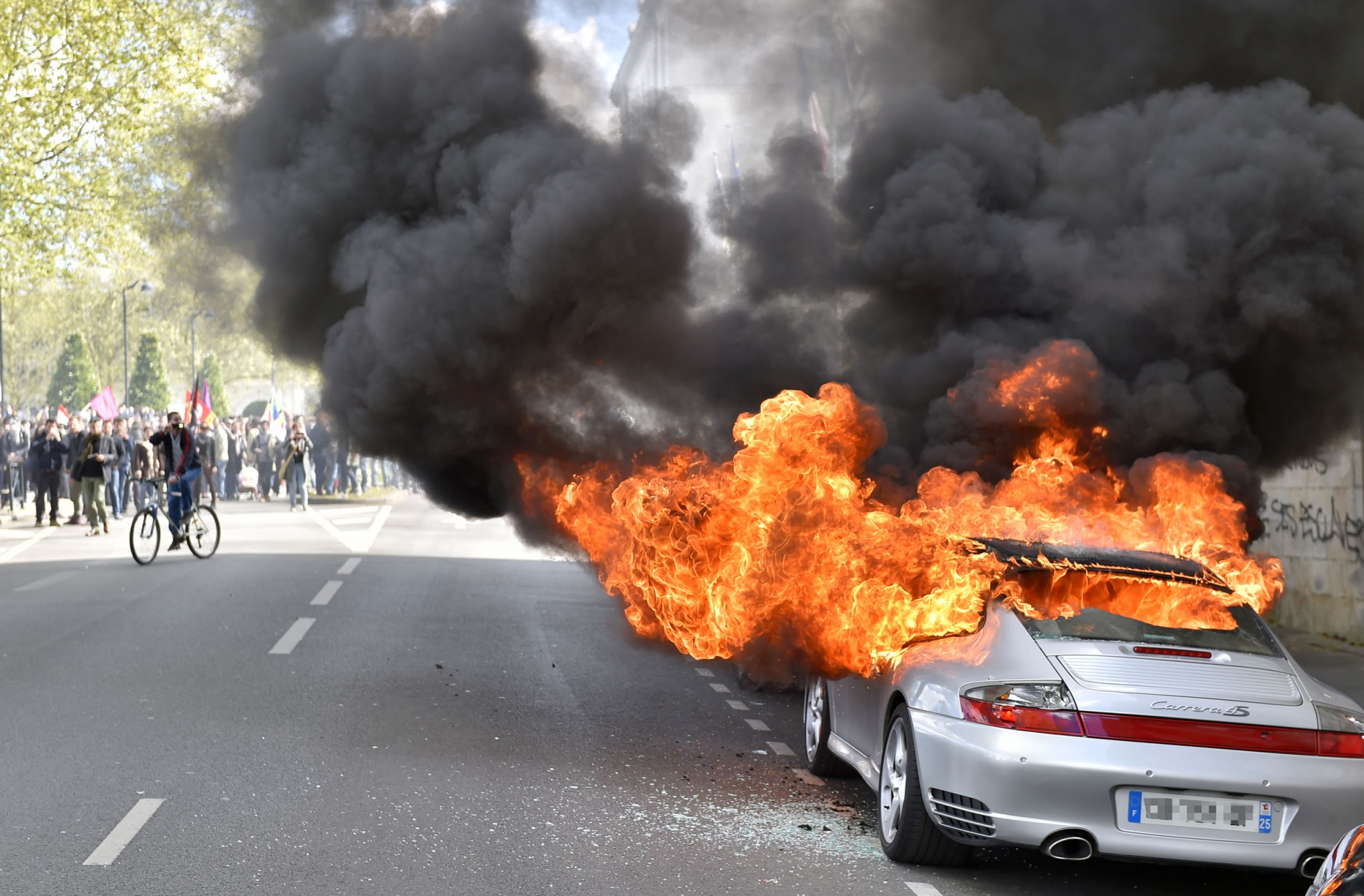 A car burns during a demonstration against the French government's proposed labour reforms on April 28, 2016 in Nantes