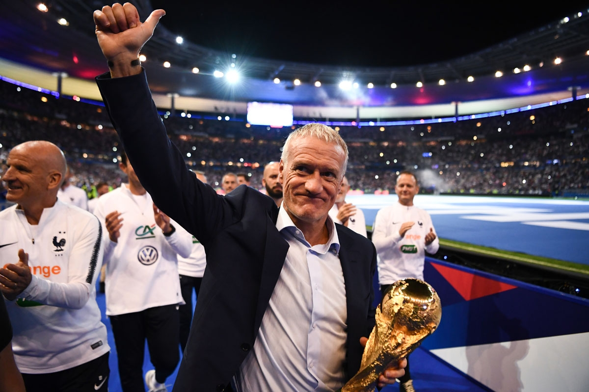 France's coach Didier Deschamps holds the 2018 World Cup trophy as he celebrates during a ceremony for the victory of the 2018 World Cup at the end of the UEFA Nations League football match between France and Netherlands at the Stade de France stadium, in