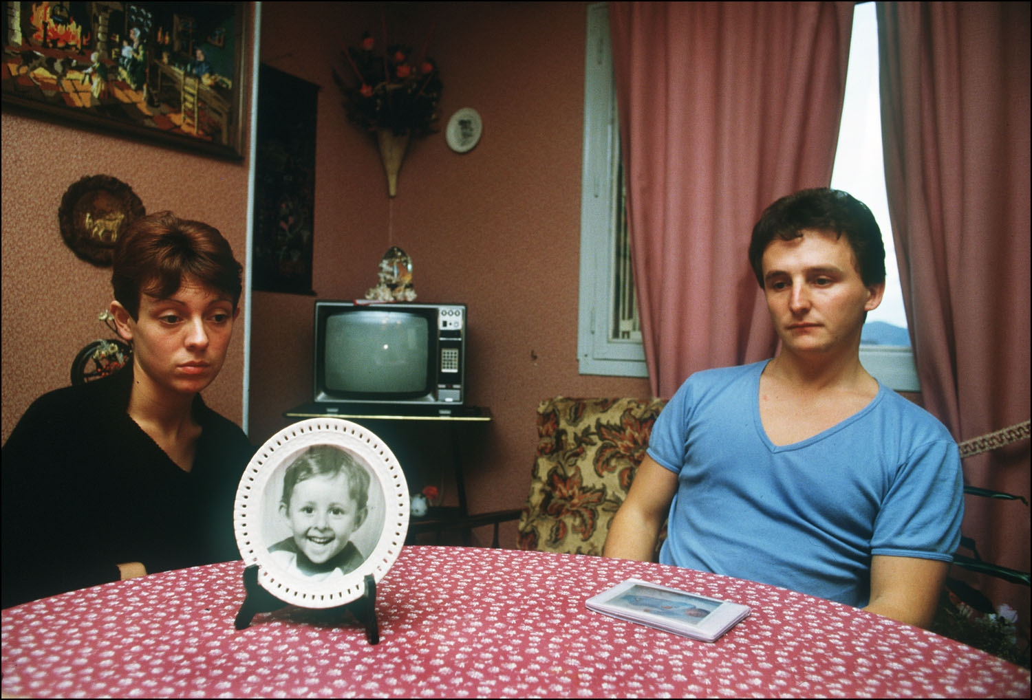 This file photo taken on November 23, 1984 shows Christine and Jean-Marie Villemin, parents of Gregory Villemin, who was found dead in the river, sitting in their living room next to a picture of their son in Epinal.