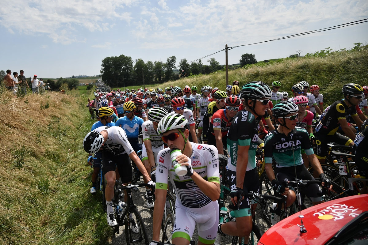Riders of the pack wait for the race to resume, after the General Director of the Tour de France halted it, following a farmers' protest who attempted to block the stage's route, during the 16th stage of the 105th edition of the Tour de France cycling rac