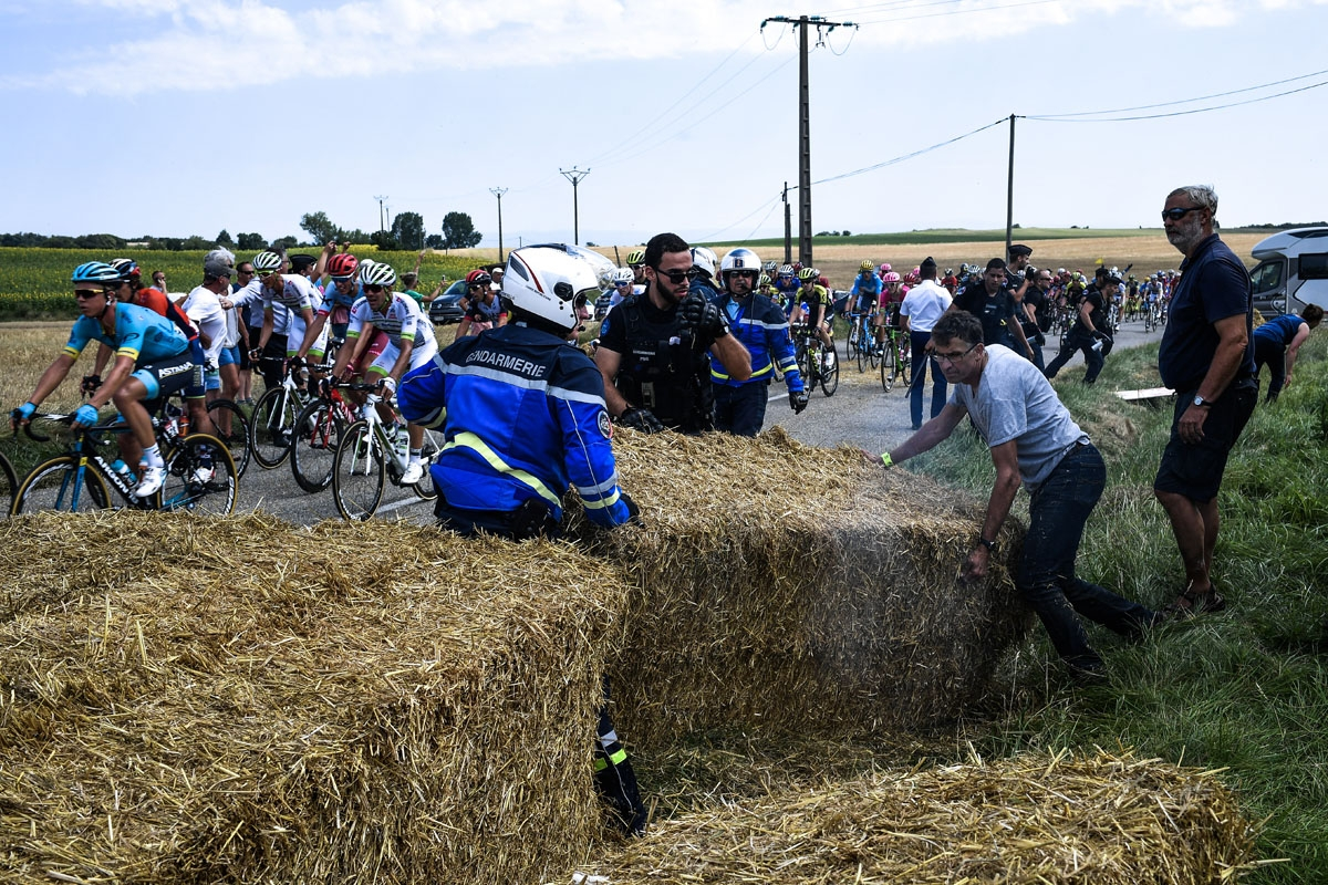 Gendarmes remove haystacks from the route as the pack rides behind, during a farmers' protest who attempted to block the stage's route, during the 16th stage of the 105th edition of the Tour de France cycling race, between Carcassonne and Bagneres-de-Luch