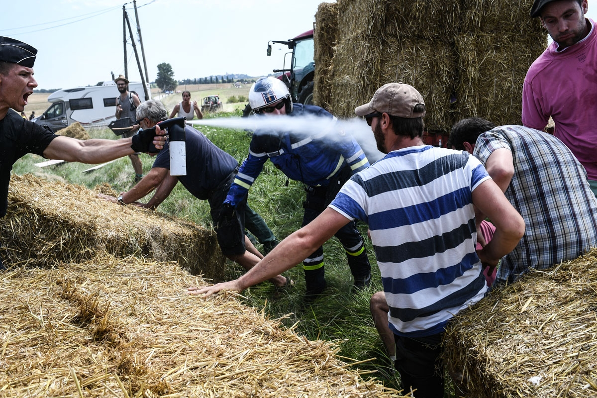 A gendarme (L) sprays tear gas at protesters (R) as other gendarmes remove haystacks from the route, during a farmers' protest who attempted to block the stage's route, during the 16th stage of the 105th edition of the Tour de France cycling race, between
