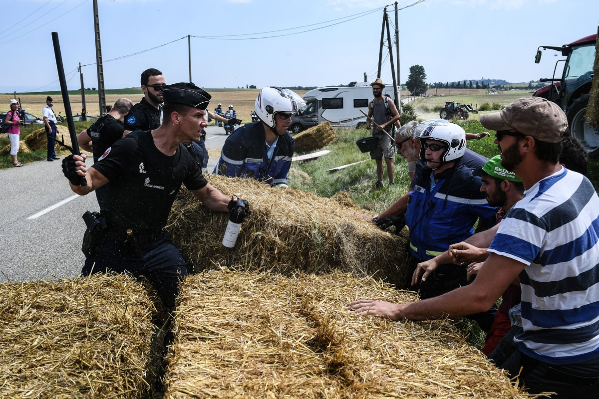 A gendarme (L) holding a baton and tear gas spray, holds back protesters (R) as other gendarmes remove haystacks from the route, during a farmers' protest who attempted to block the stage's route, during the 16th stage of the 105th edition of the Tour de