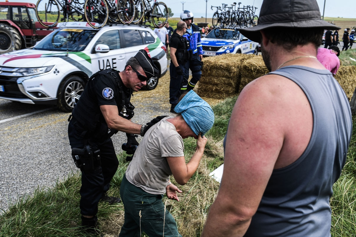 A protester (C) reacts after scuffling with gendarmes (R and L) during a farmers' protest who attempted to block the stage's route, during the 16th stage of the 105th edition of the Tour de France cycling race, between Carcassonne and Bagneres-de-Luchon,