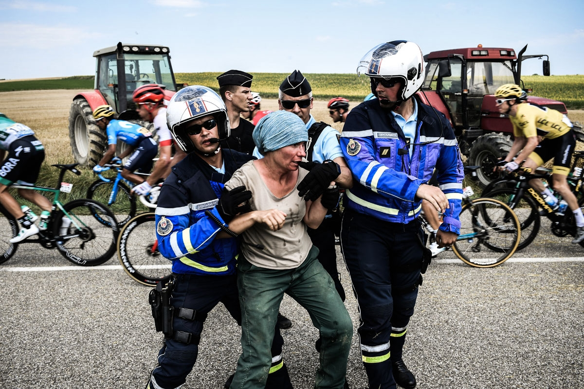 Gendarmes detain a protester as Great Britain's Geraint Thomas (R), wearing the overall leader's yellow jersey, and the pack ride behind, during a farmers' protest who attempted to block the stage's route, during the 16th stage of the 105th edition of the