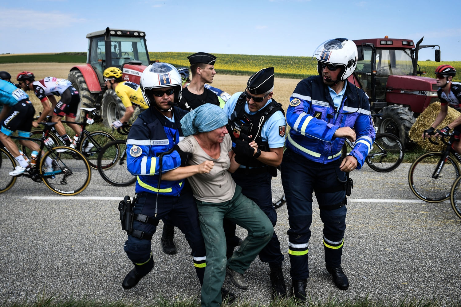 Gendarmes detain a protester as Great Britain's Geraint Thomas (3rdL), wearing the overall leader's yellow jersey, and the pack ride behind, during a farmers' protest who attempted to block the stage's route, during the 16th stage of the 105th edition of
