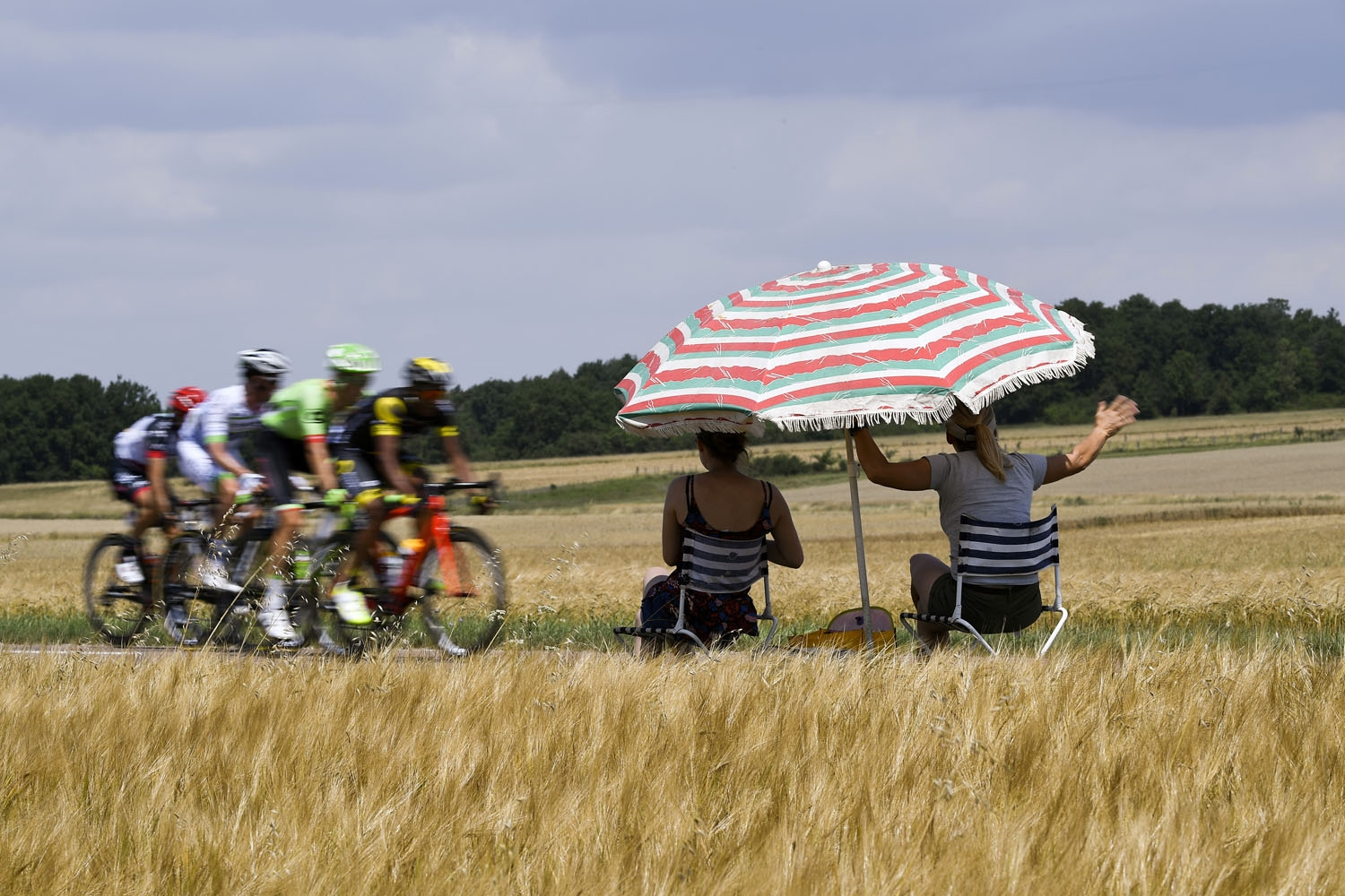 Supporters sitting under a parasol look at the breakaway riding during the 213,5 km seventh stage of the 104th edition of the Tour de France cycling race on July 7, 2017 between Troyes and Nuits-Saint-Georges
