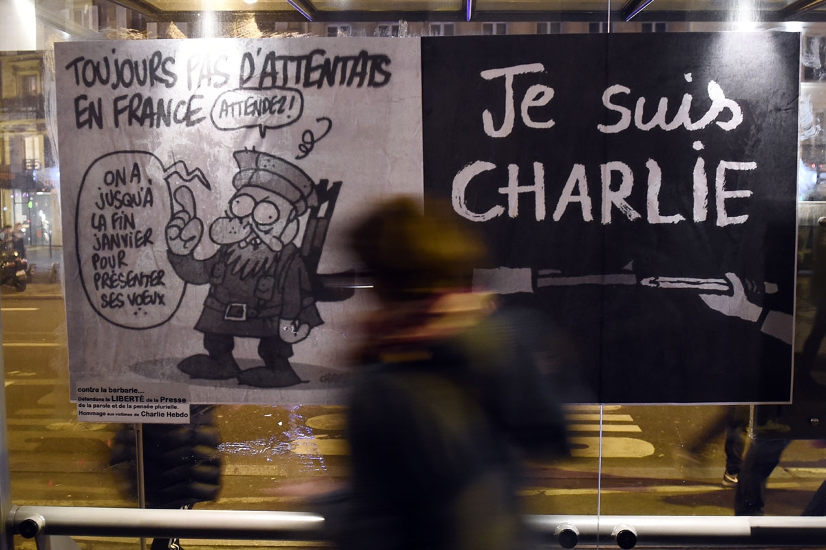 (FILES) This file photo taken on January 7, 2015 shows a woman walking by a poster bearing the last cartoon of late cartoonist Charb sticked on a bus station in Paris, following an attack by unknown gunmen on the offices of the satirical weekly, Charlie H