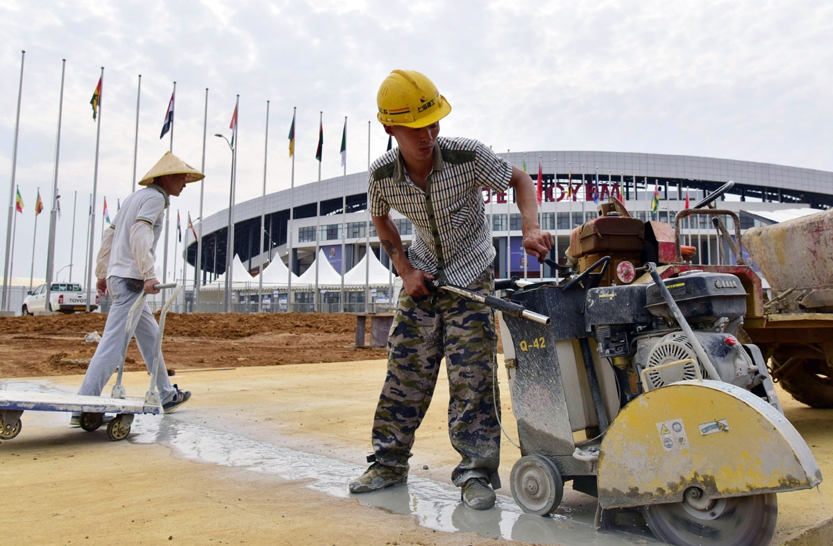 A photo taken on January 18, 2017, shows men working outside Oyem Stadium (Stade d'Oyem) one of the four stadiums hosting matches during the 2017 Africa Cup of Nations football tournament in Gabon.
