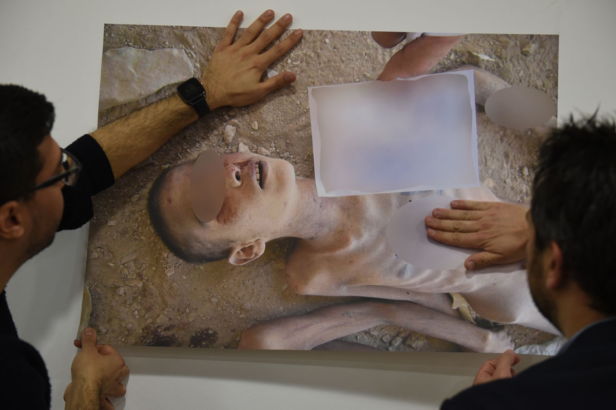 Members of the Syrian Organisation for the Victims of War (SOVW) display pictures documenting the torture of detainees inside the Assad regime's prisons and detention centres, on March 17, 2016 in Geneva. The photographs were taken by a former military