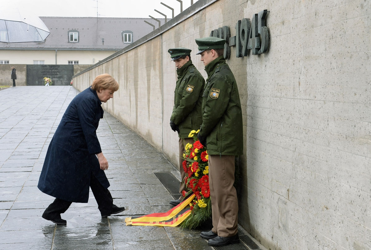 German Chancellor Angela Merkel bows to adjust the ribbons of a wreath laid in her name in front of the International Memorial of former Nazi concentration camp of Dachau, southwestern Germany, during a ceremony to mark 70 years since it was liberated by