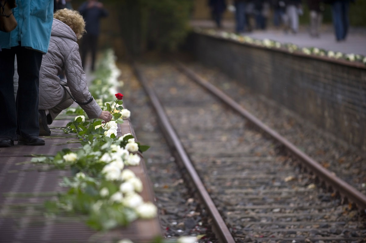An elderly woman lays a flower at Berlin's Platform 17 memorial during a cermony marking the 70th anniversary of the departure of the first convoys carrying Jews to concentration camps from the Berlin Gruenewald station, October 18, 2011.
