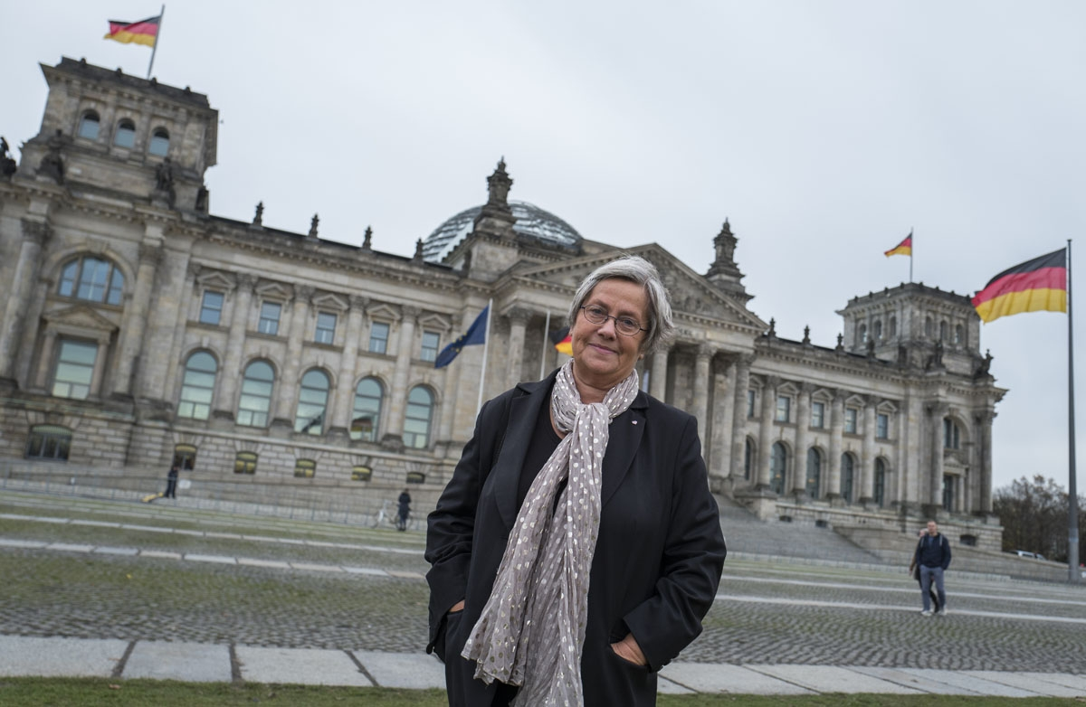 Karin Felix, who served as a guide at the Reichstag parliament building for a quarter-century, poses in front the Reichstag builing in Berlin on November 23, 2017.