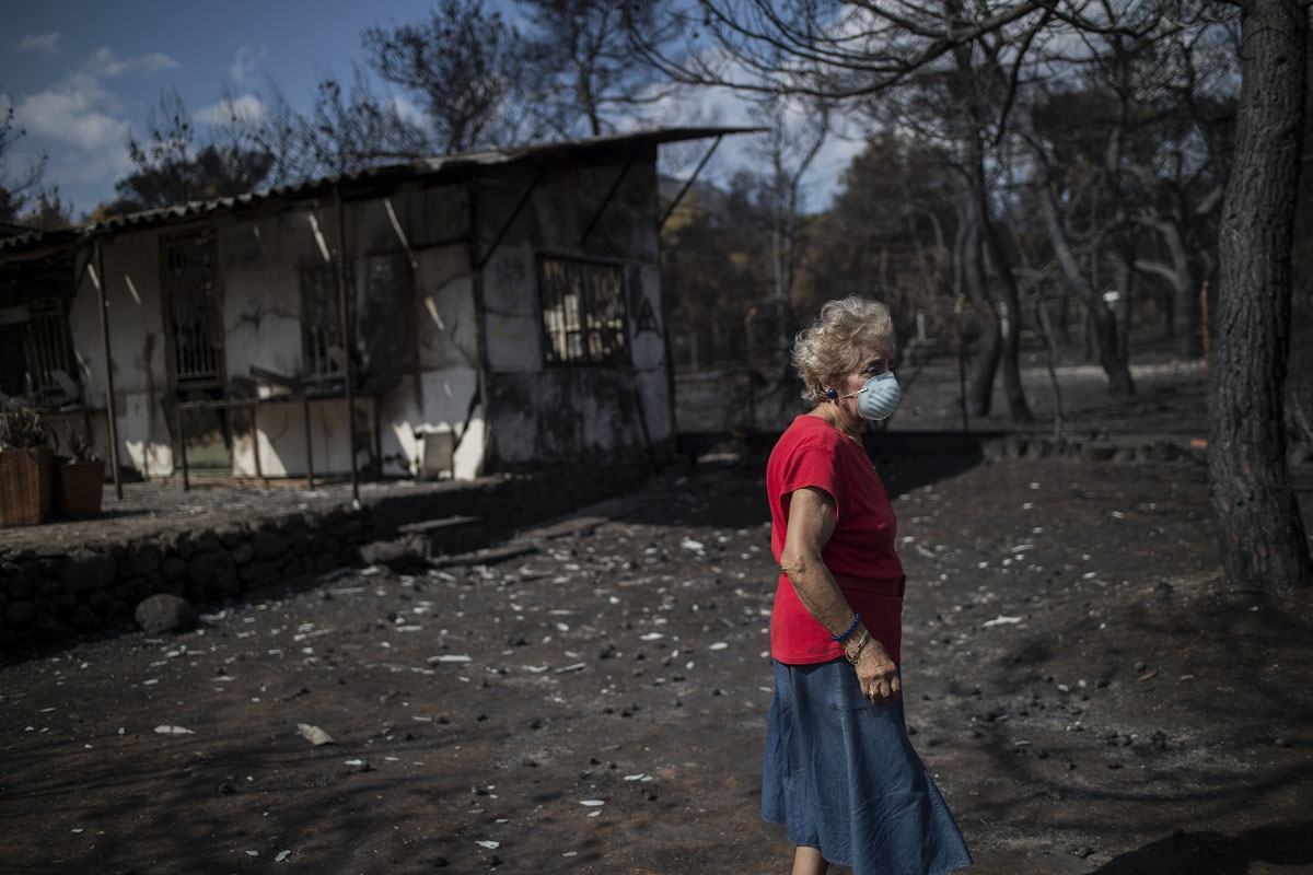 A woman wearing a mask walks in front of her burnt house following a wildfire at the village of Neos Voutzas, near Athens, on July 26, 2018.