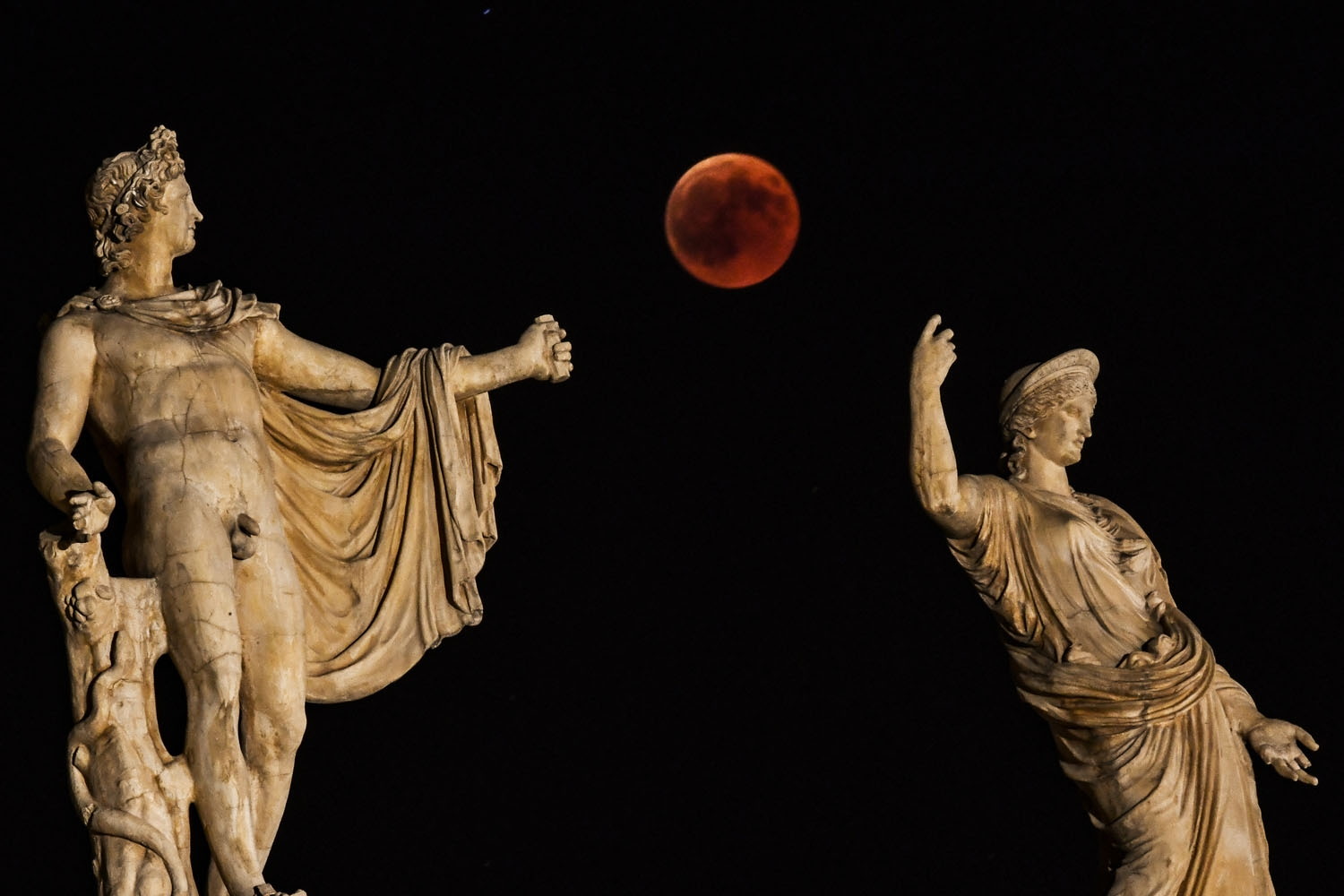 A picture shows the full moon during a blood moon eclipse beside a statue of ancient Greek goddes Hera (R) and god Apollo in central Athens on July 27, 2018.