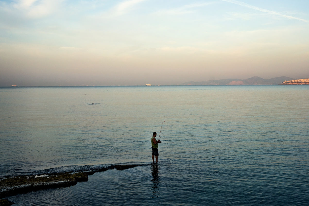 A man fishes off a rock on the beach of Faliro in Athens on October 2, 2016