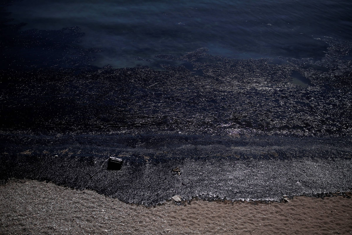 This picture taken on September 12, 2017 shows oil that has washed ashore on a beach of Salamis island near Athens, after an old tanker sank close to Salamis island over the weekend.