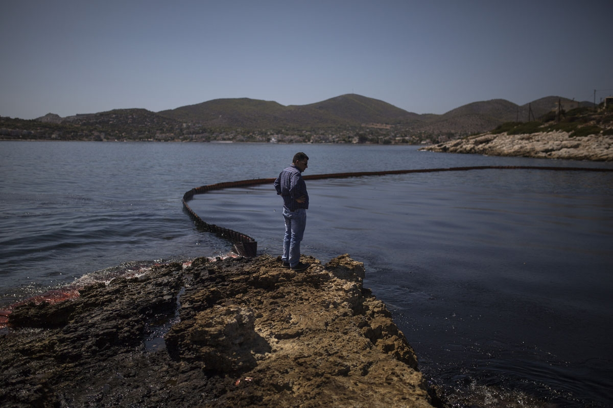A man looks at an oily sea on September 12, 2017 on Salamis island near Athens, after an old tanker sank close to Salamis island over the weekend.