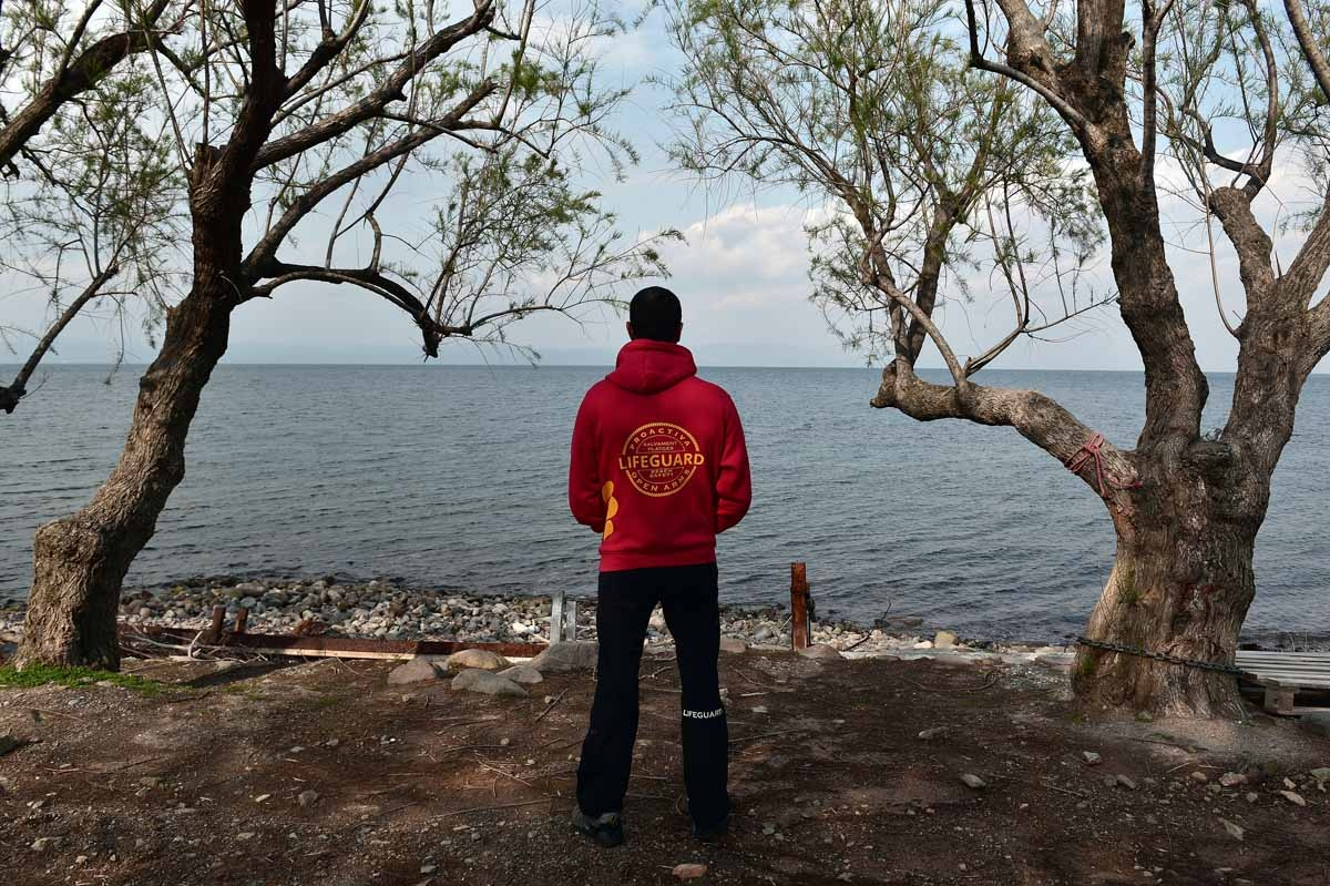 A Member of the Proactiva Open Arms rescue team looks at the sea at their base near Skala Sykamiasn on the island of Lesbos on March 15, 2017 almost a year after an EU-Turkey deal.