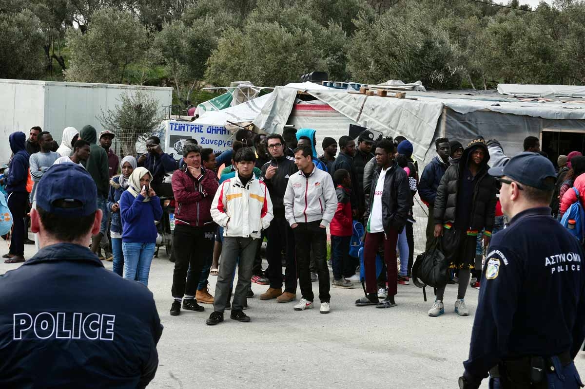 A picture taken on March 16, 2017 shows policemen standing guard near migrants at the  Moria migrant camp on the island of Lesbos, almost a year after an EU-Turkey deal.