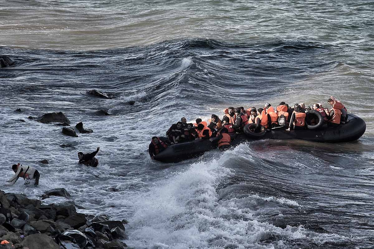 Refugees and migrants try to reach the shore on the Greek island of Lesbos, despite a rough sea, on October 30, 2015, after crossing the Aegean sea from Turkey.