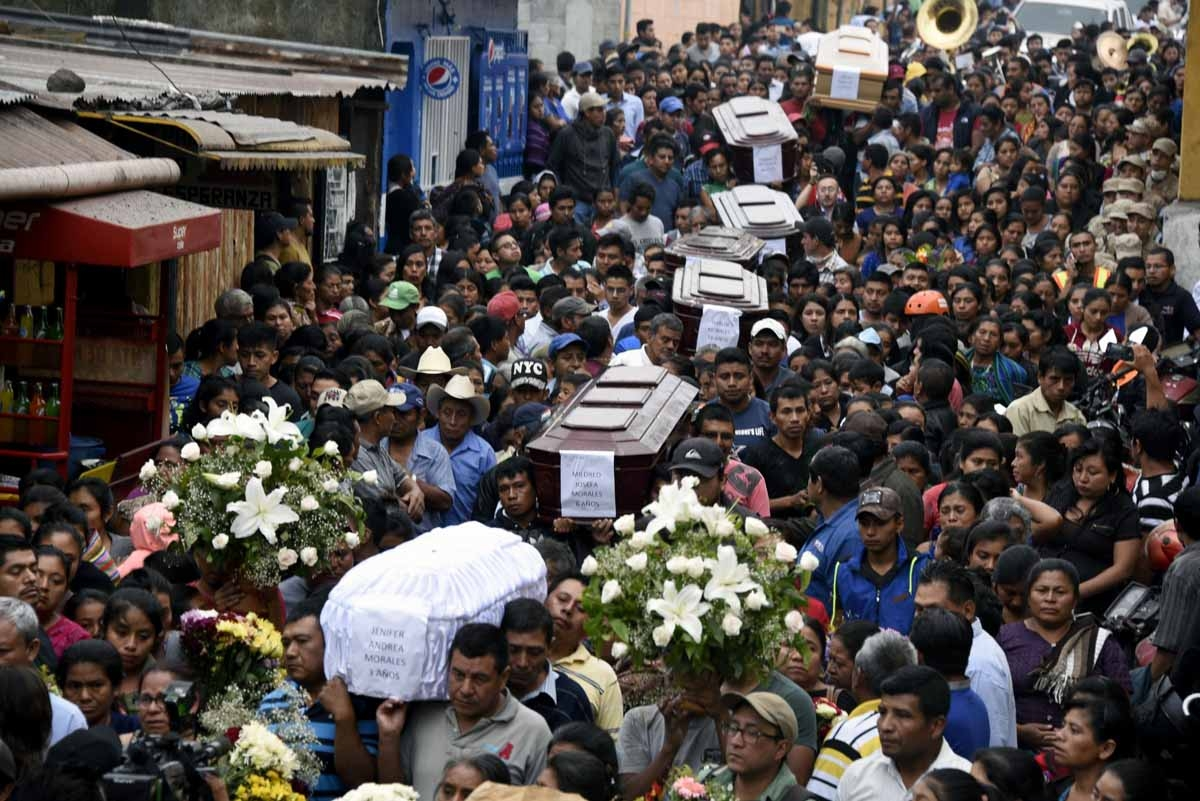 People carries the coffins of seven people who died following the eruption of the Fuego volcano, at the streets of Alotenango municipality, Sacatepequez, about 65 km southwest of Guatemala City, on June 4, 2018. Rescue workers Monday pulled more bodies fr