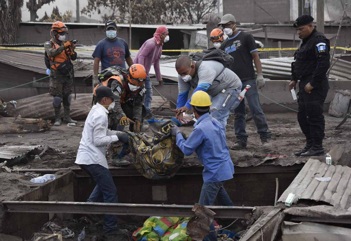 Rescuers carries part of the body of a victim of the Fuego Volcano eruption, recovered during a search in the ash-covered village of San Miguel Los Lotes, in Escuintla department, about 35 km southwest of Guatemala City, on June11, 2018. A week after Guat
