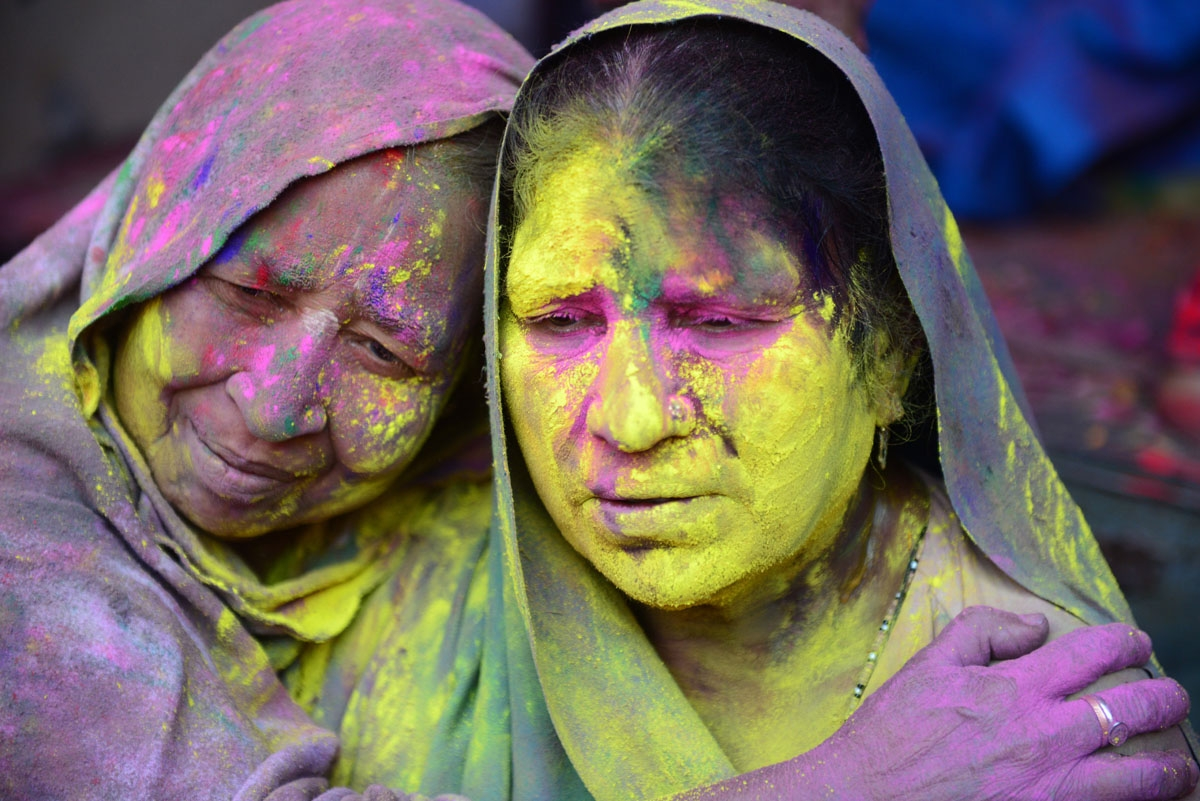 Indian widows celebrate Holi or the festival of colors in Vrindavan on March 9, 2017. Widows congregated on a small patio of the Govinath temple in which they live and danced and played with colored powder to celebrate the occasion. / AFP